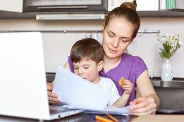 Mother freelancer on maternity leave works with documentation, makes business report on portable laptop computer, holds son who interrupts her, sit together against kitchen interior. Family concept