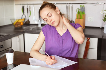 Fatigue adorable woman has pain in neck, being overworked, writes in papers, sits against kitchen inerior with takeaway coffee. Busy young tired beautiful housewife makes financial report at home