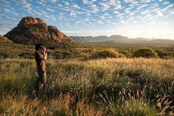 Young Asian male photographer taking photo of beautiful sunrise in savanna (savannah) woodland, Namibia, Africa. Travel photography concept