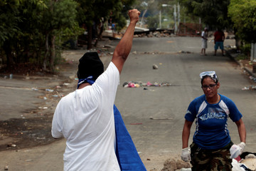 University student holds up arm during protest in Managua