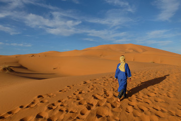BERBER MAN IN NATIONAL CLOTHES WALKING IN THE SAHARA DESERT. MERZOUGA MOROCCO. MARCH 2018