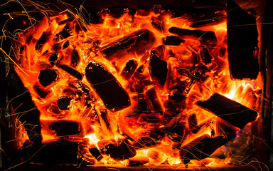 bright orange sparks from a campfire on long exposure and smoldering coals. dynamics lines traces.