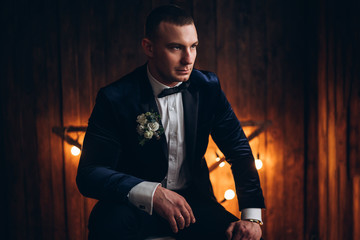 Portrait of young groom with wooden background