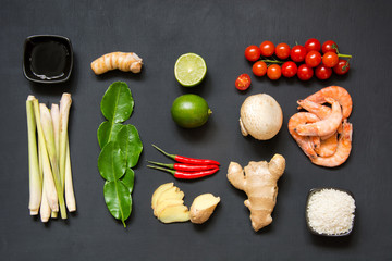 Ingredients for popular Thai soup Tom-yum kung. Lime, galangal, red chili, cherry tomato, lemongrass and kaffir lime leaf on black board . Flat lay. Top view.