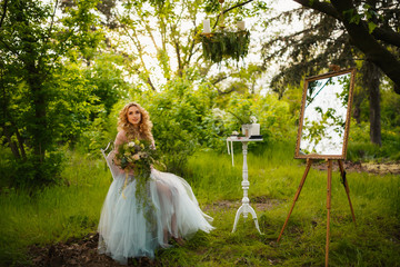 bride in peignoir with bouquet of hydrangeas sitting in woods
