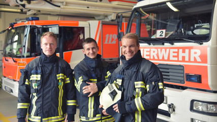 Portrait einer Gruppe Feuerwehrmänner vor den Einsatzfahrzeugen auf der Feuerwache // Portrait of a group of firefighters in front of the fire station vehicles