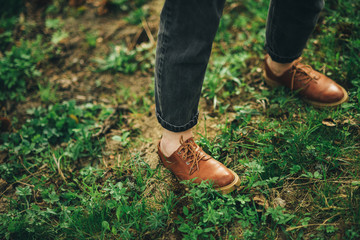 stylish person is staying on the grass in leather shoes