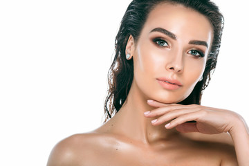 Beauty Woman Portrait. Beautiful brunette woman with perfect fresh clean skin and wet hair posing and looking at camera. Spa and Skin Care Concept