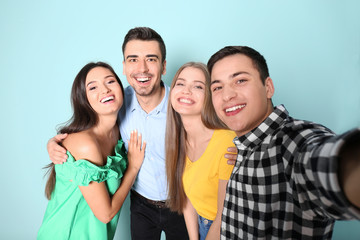 Young happy friends taking selfie against color background