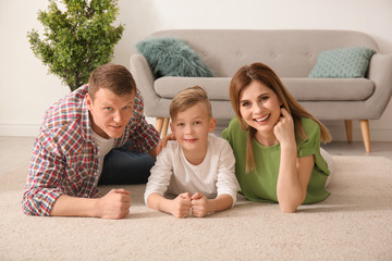 Happy family lying on cozy carpet at home
