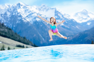 Child in outdoor swimming pool of alpine resort