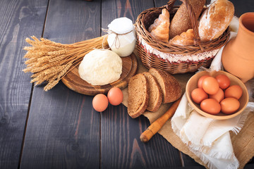 Breakfast from farm products: eggs, milk, bread on a wooden table.