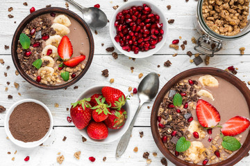 cocoa or chocolate and banana protein smoothie bowls with granola, strawberry and pomegranate seeds served for breakfast