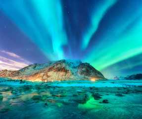 Poster Green blue Aurora. Northern lights in Lofoten islands, Norway. Starry sky with polar lights. Night winter landscape with aurora, sea with sky reflection, stones, sandy beach and mountains. Green aurora borealis