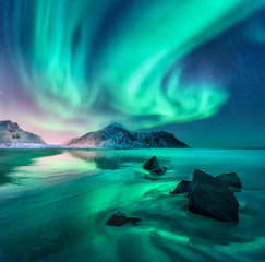 Poster Green blue Aurora. Northern lights in Lofoten islands, Norway. Sky with polar lights, stars. Night winter landscape with aurora, sea with sky reflection, stones, sandy beach and mountains. Green aurora borealis