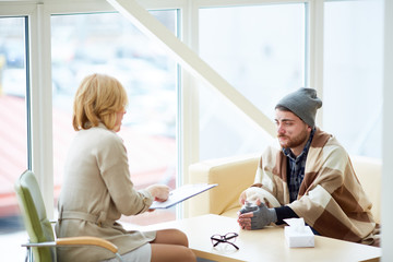 Psychologist or social worker having talk to one of refugees or homeless people in the center of support