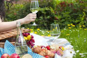 Wine and croissants on a picnic. A glass of wine in a woman's hand. Tasty food. Romantic weekend. Free space for text