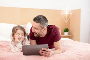 Spending time together. Happy loving daddy spending time with his daughter and watching a film