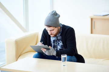 Young migrant in shabby clothes filling in all necessary documents to have social help and payment