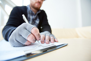 Dirty hands holding pen while writing down some social information in document giving right for regular help and payments