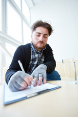 Young migrant looking for social help in foreign country while filling in all the necessary documents in support center