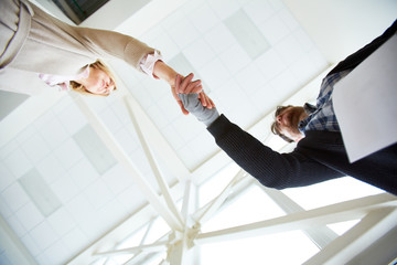 Below view of social worker and migrant hands in handshake as symbol of help and support