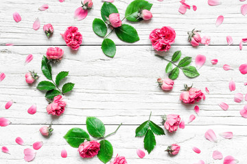 Flowers composition. Frame made of fresh rose flowers on white wooden background. Flat lay. mock up