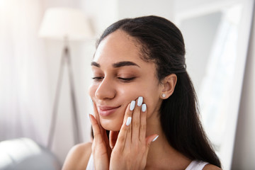 For healthy skin. The close up of a gorgeous dark-haired woman stretching the skin of her cheeks while doing a face-lifting massage