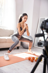 Wannabe vlogger. Beautiful slim woman recording herself on camera while doing squats in her living room
