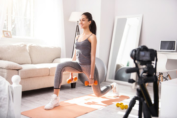 Proper stretching. Joyful slim woman doing lunges and holding dumbbells while filming herself on camera