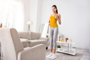 Content with results. Beautiful young woman standing on the scales and weighing herself while showing thumbs up and being satisfied with the result