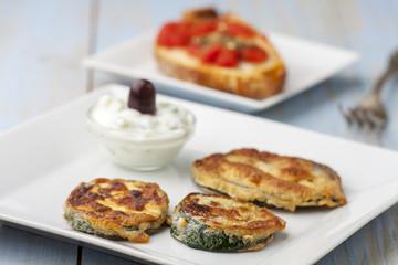 Gebackene Zucchini mit Tsaziki auf Teller