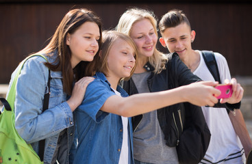 teenagers taking pictures of themselves on smartphone