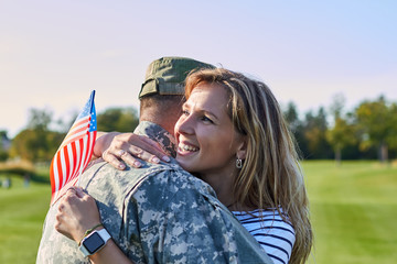 American soldier is hugging with wife. Happy smiling woman is embracing her military husband.