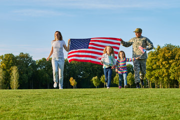 Soldier and his family are walking walking american flags. Front view, american patriots on the park meadow.