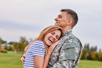 Married soldier hugging wife outdoor. Woman is very happy her husband is back from the army.