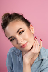 Natural beauty. Portrait of optimistic young woman is sitting and looking at camera with smile. She is touching her neck. Isolated on pink background