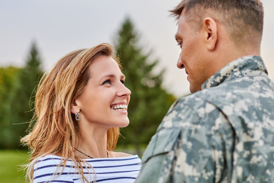 Touching moment soldier returning from army. Happy meeting outdoor, lovely gaze, mature couple.