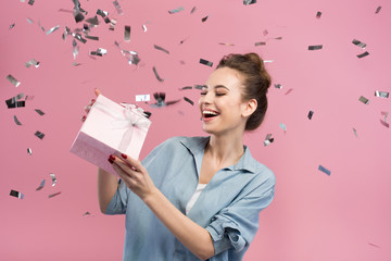 Happiness. Cheerful cute girl is demonstrating gift box being surrounded by confetti. She is expressing gladness. Pink background