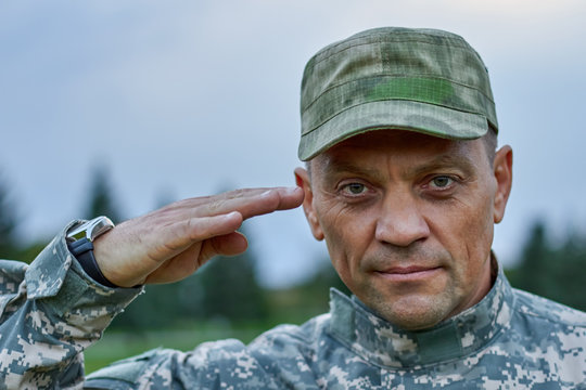 Close up portrait of serious soldier saluting. Strong man serving to his country with pride.