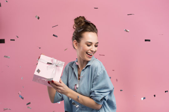 Happy day. Joyful attractive young woman is holding gift while being surrounded by confetti. She is feeling delight. Pink background