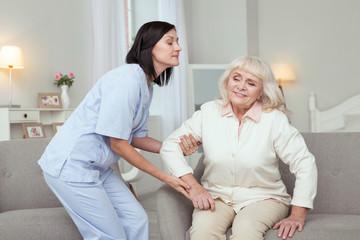 Social work. Beautiful caregiver helping senior woman who sitting on sofa