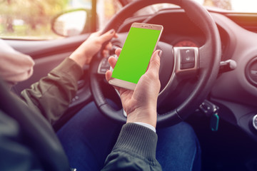 An unidentified woman sitting at the wheel of car and holding smartphone with green screen. Chroma key. Copy space