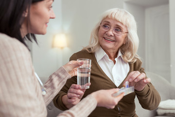 Individual treatment. Happy senior woman taking pills from nurse while smiling