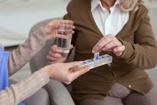 Drug usage. Close up of attractive female hand holding container for medication while giving glass with water to elder woman