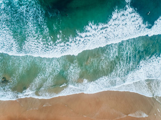 Aerial view of people surfing on a beach in Asturias