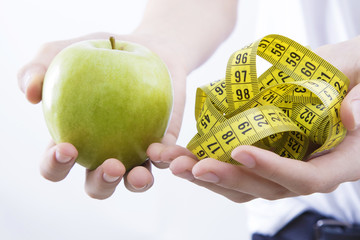 hands with tape measure and Apple, concept of healthy diet and slimming