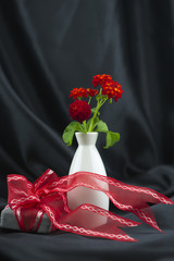 Gift with red ribbon against background of black satin and red lantana flowers