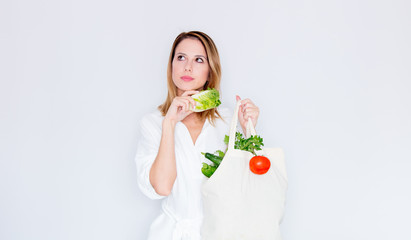 woman in white clothes holding bag with different vegetables
