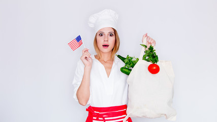 woman in cook uniform holding bag with different vegetables and american flag